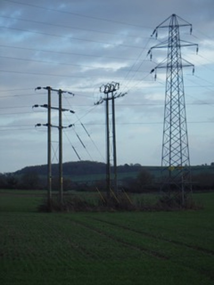 3 different sized power poles and pylons in a field
