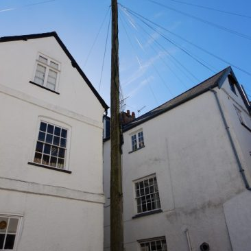A courtyard in Topsham in Devon with an enormous telegraph pole. How did it get there>