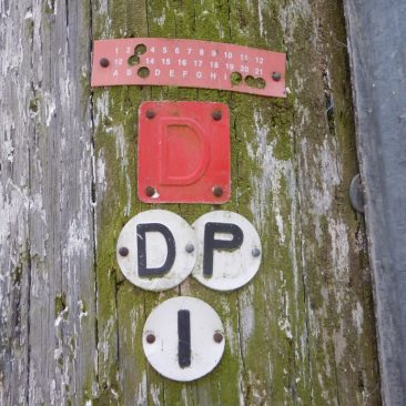 The markings on a very tall telegraph pole in a courtyard in Topsham showing a D plate.
