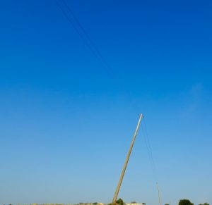 A leaning telegraph pole underneath an azure sky
