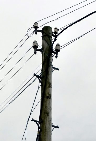 Close up of 4 cordeaux insulators atop a lonely pole in West Wales