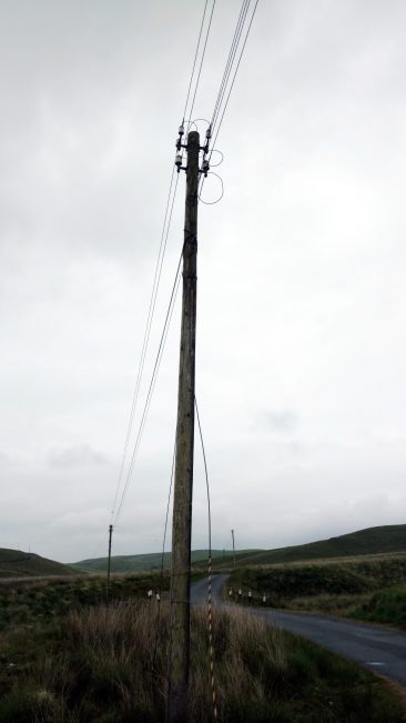A simple telegraph pole with 4 insulators on lonely road in Wales