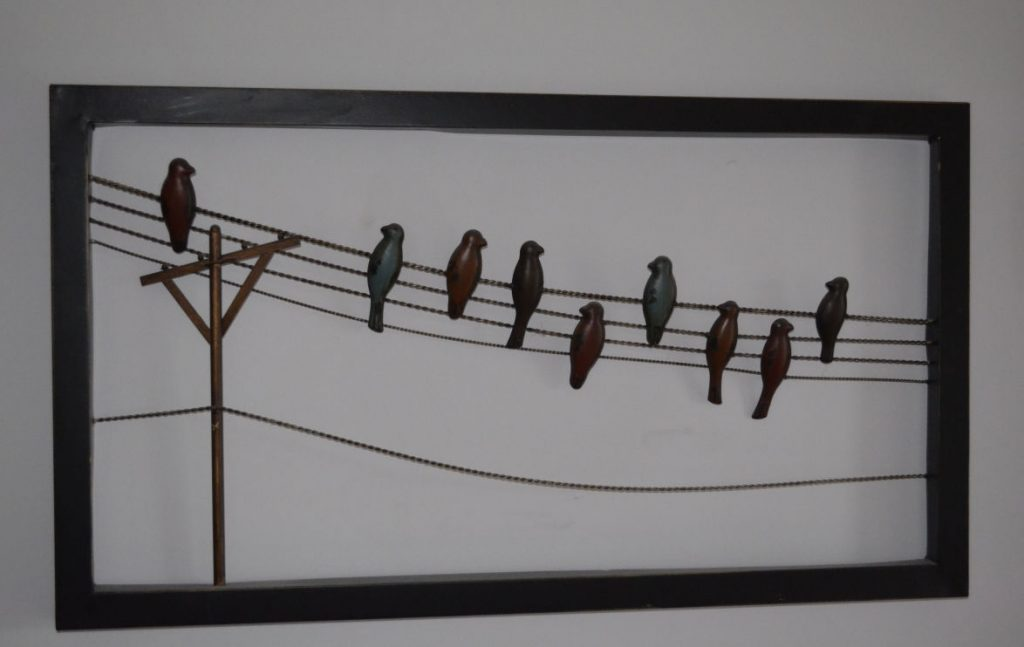An all-metal wall art featuring birds on a telegraph wires with a pole.